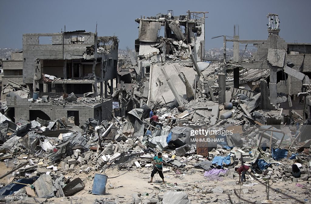 Palestinian men walk on the rubble of their destroyed houses in the Tufah neighbourhood in eastern Gaza City on August 31 following a 50day war...