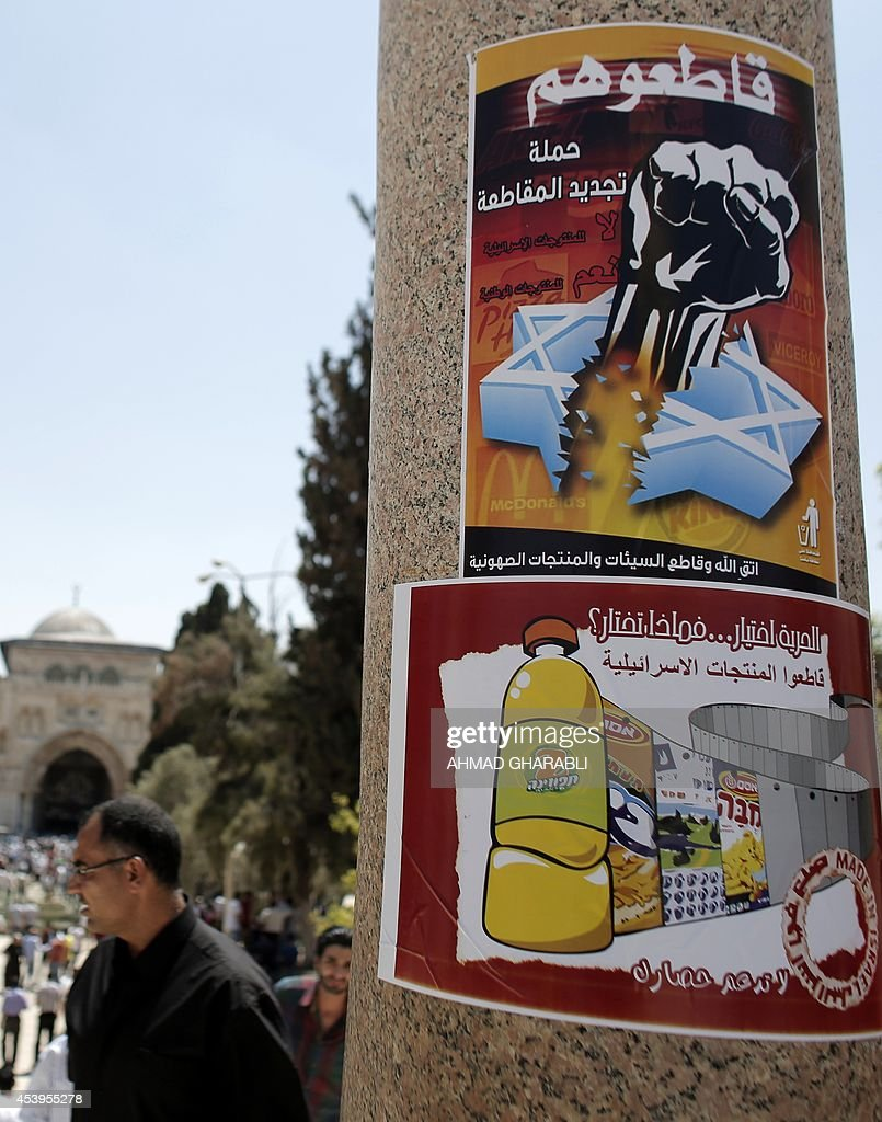 Palestinian men walk past a poster at the al-Aqsa mosque compound, Islam's third most holy site, in Jerusalem's old city, calling for people to boycott Israeli goods following the latest conflict between Hamas militants and Israel in the Gaza Strip, on August 22, 2014. Known as the BDS movement -- boycott, divestment and sanctions -- it aims to put political and economic pressure on Israel over its occupation of the Palestinian territories in a bid to repeat the success of the campaign which ended apartheid in South Africa.