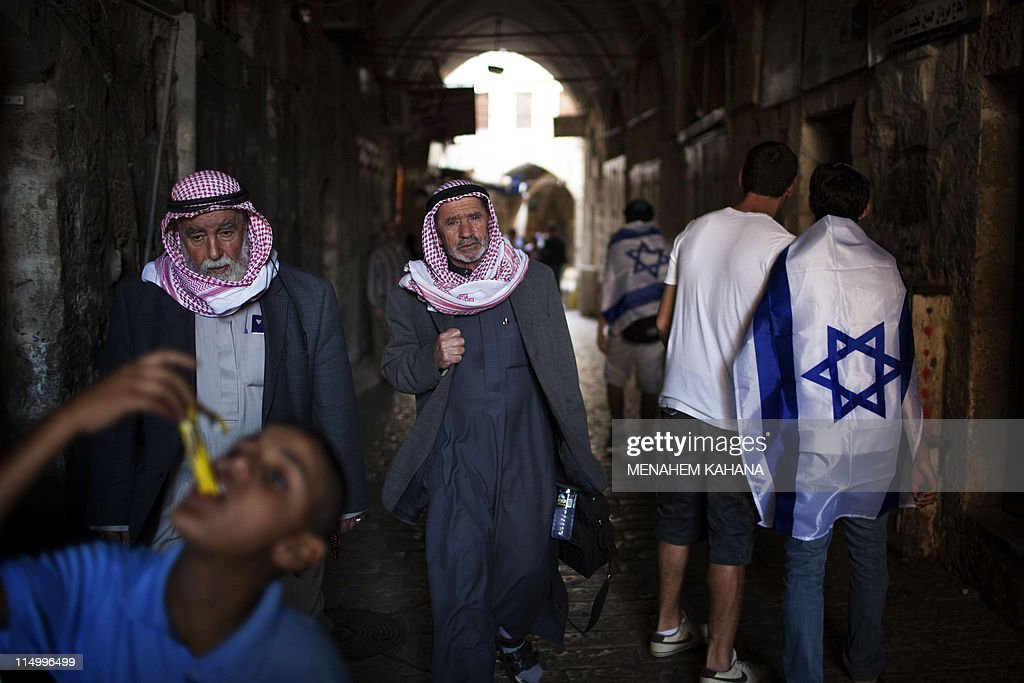 Palestinian men walk past Israeli youth marching in the old city of Jerusalem on June 1 2011 during the Jerusalem Day parade in the city's mainly...