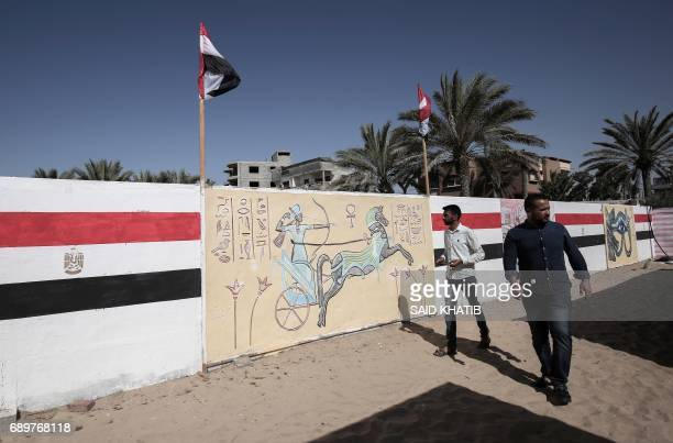 Palestinian men walk past mural drawings of Pharaonic figures and Egypt's national flag at a technical site in the southern Gaza Strip town of Rafah...