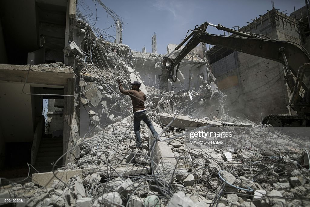 Palestinian men work on the remains of a building destroyed during the 50-day war between Israel and Hamas-led militants in the summer of 2014, on April 30, 2016, in Gaza City. Reconstruction aid to over 1,000 families in Gaza has been suspended due to a lack of materials, the United Nations said on April 28, after Israel banned the private import of cement over corruption claims. / AFP / MAHMUD