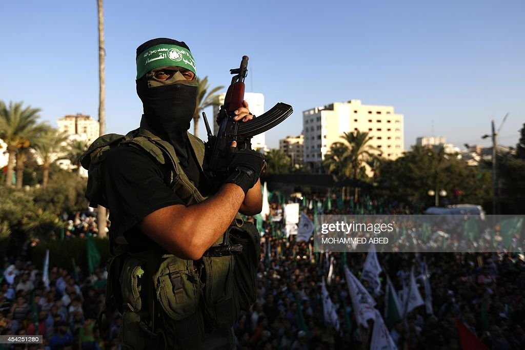 A Palestinian militant from the Ezzedine al-Qassam Brigades (L), Hamas' armed wing, attends a rally in Gaza City on August 27, 2014, following a deal hailed by Israel and the Islamist movement as 'victory' in the 50-day war. The agreement, effective from 1600 GMT on August 26, saw the warring sides agree to a 'permanent' ceasefire which Israel said would not be limited by time, in a move hailed by Washington, the United Nations and top world diplomats.