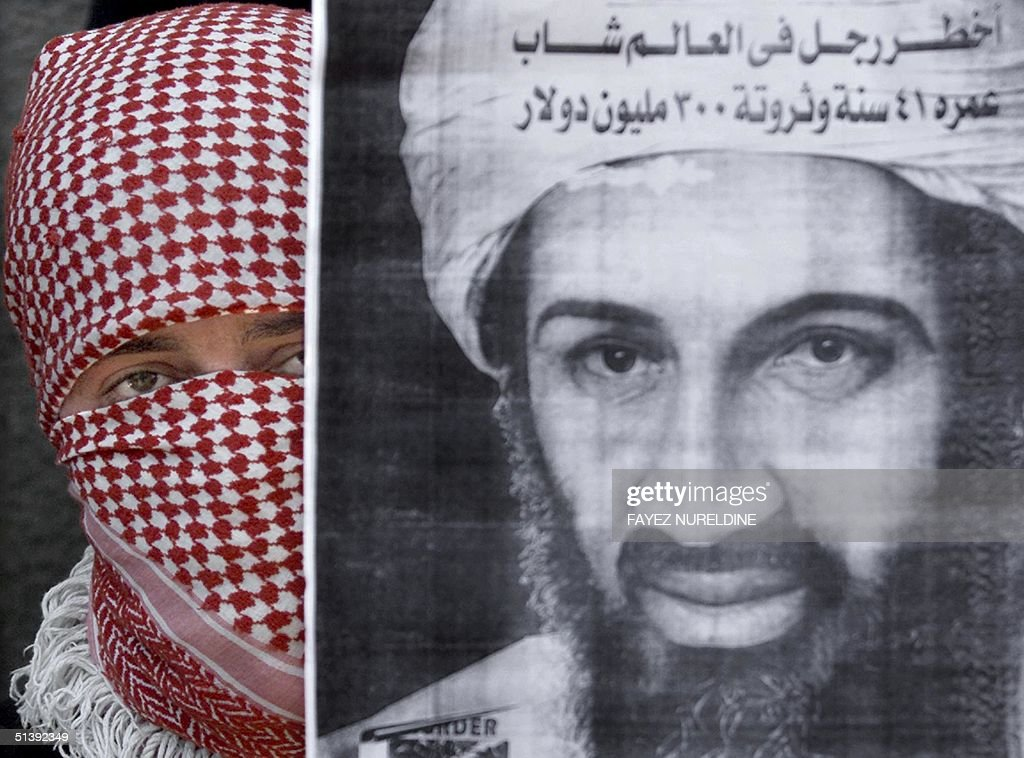 A Palestinian militant from the Islamic Jihad movement displays a portrait of Saudi dissident Osama bin Laden during the funeral of Palestinian youth Ahmad Yassin in Gaza City 02 July 2001. The 15-year-old boy was shot in the neck last week by Israeli troops in clashes near the Karni border crossing, east of Gaza Cit, and died of his wounds 01 July.