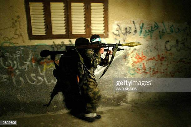 Palestinian militant from the radical Islamic Hamas movement armed with a Rocket Propelled Grenade takes a position during an Israeli army raid at...