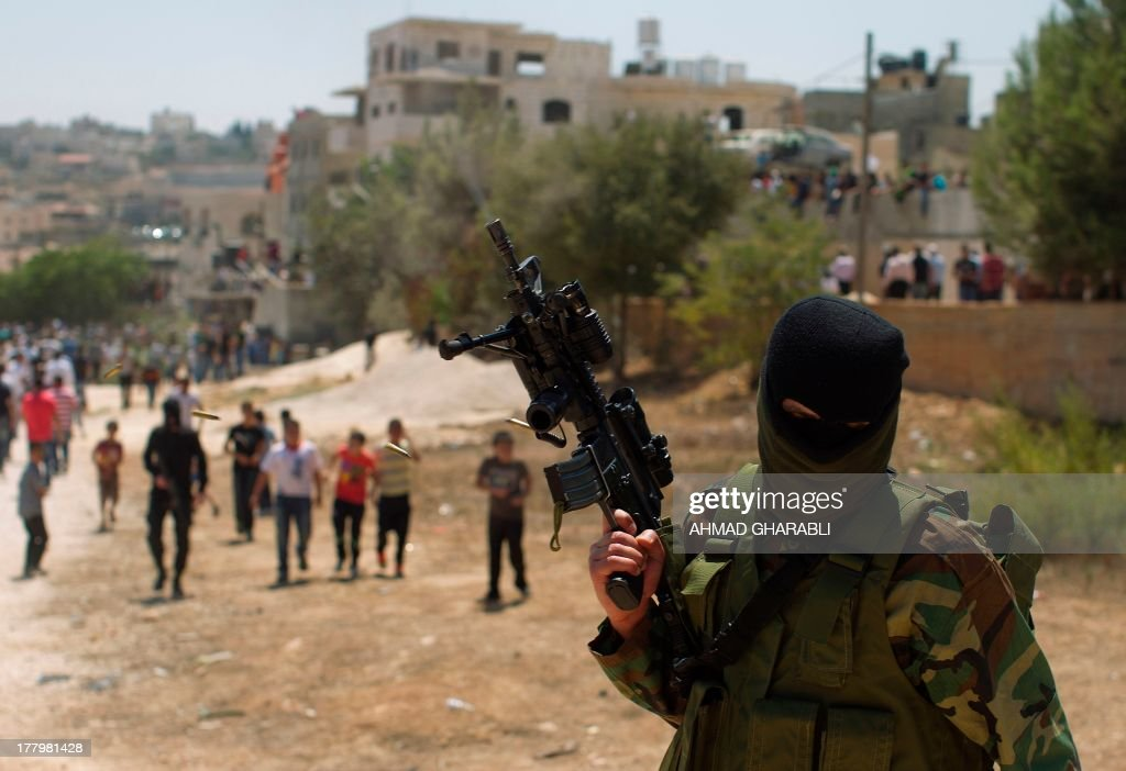 A Palestinian militant holds up his automatic machine gun as fires into the air in the city of Ramallah during the funeral procession of three Palestinian youths who were killed during clashes with Israeli security forces in the West Bank's Qalandia refugee camp on August 26, 2013. Expected peace talks between Israeli and Palestinian negotiators were cancelled after Israeli security forces shot dead three Palestinians during clashes in the West Bank, a Palestinian official said.