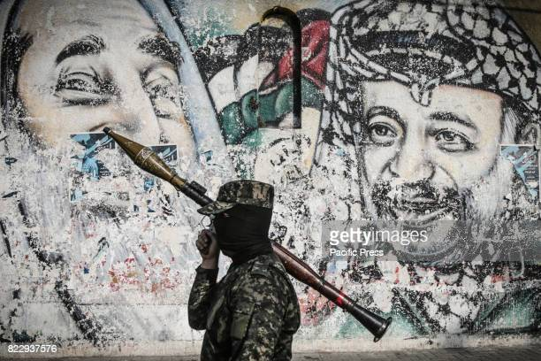Palestinian militant of the EzzAl Din Al Qassam Brigades the armed wing of Palestinian Hamas movement walks next to the graffiti of the late...