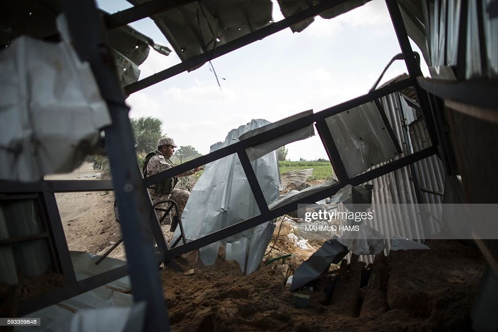 A Palestinian militant of the Islamic Jihad movement inspects the rubble of a makeshift dwelling on August 22 2016 in Beit Lahia in the northern Gaza...