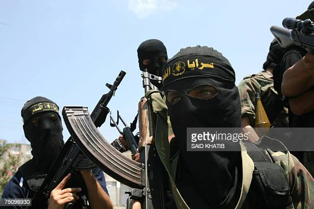 Palestinian militants from Islamic Jihad march during the funerals of nine of the eleven fighters killed during an Israeli military operation into...