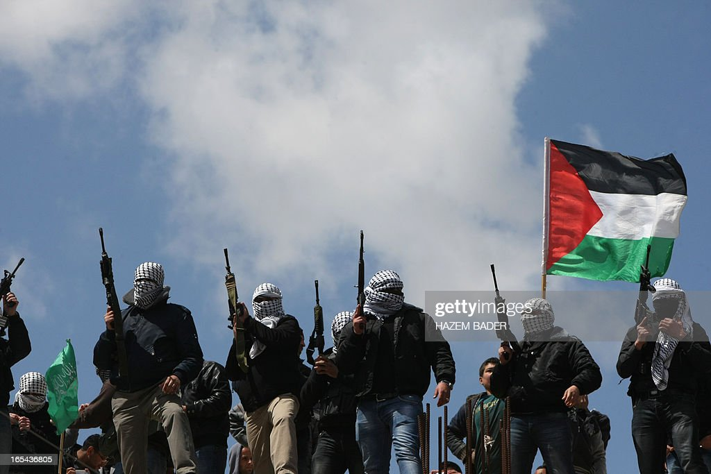Palestinian militants from the al-Aqsa Martyrs Brigade hold up their weapons during the funeral of Maisara Abu Hamdiya, a Palestinian prisoner who died of cancer while in Israeli detention, as his body carried outside the Mosque in the West Bank city of Hebron April 4, 2013. The West Bank simmered with anger as thousands joined the funeral of a prisoner who died in an Israeli jail and similar numbers gathered to bury two teens shot dead overnight. AFP PHOTO/HAZEM BADER