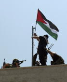 Palestinian militants from the alAqsa Martyrs display Palestinian and Fateh flags on the Palestinian legislative council building on June 16 2007 in...