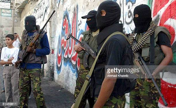 Palestinian militants from the AlAqssa Fateh movement stand with their weapons ready October 10 2004 in the Jabalya refugee camp north of the Gaza...