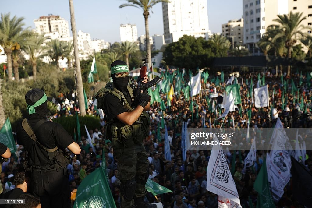 Palestinian militants from the Ezzedine al-Qassam Brigades (L), Hamas' armed wing, attend a rally in Gaza City on August 27, 2014, following a deal hailed by Israel and the Islamist movement as 'victory' in the 50-day war. The agreement, effective from 1600 GMT on August 26, saw the warring sides agree to a 'permanent' ceasefire which Israel said would not be limited by time, in a move hailed by Washington, the United Nations and top world diplomats.