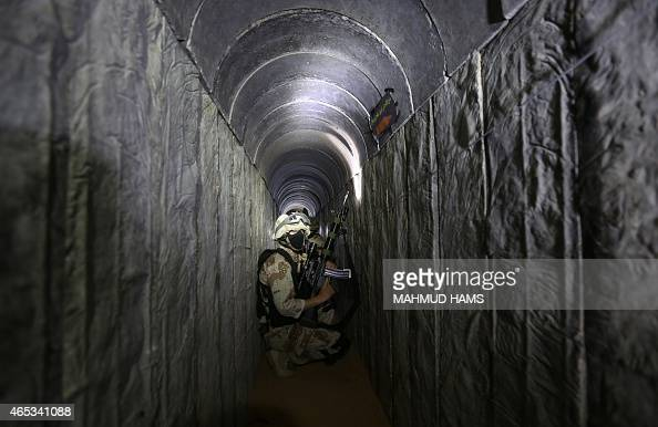 Palestinian militants from the Islamic Jihad's armed wing the AlQuds Brigades squat in a tunnel used for ferrying rockets and mortars back and forth...