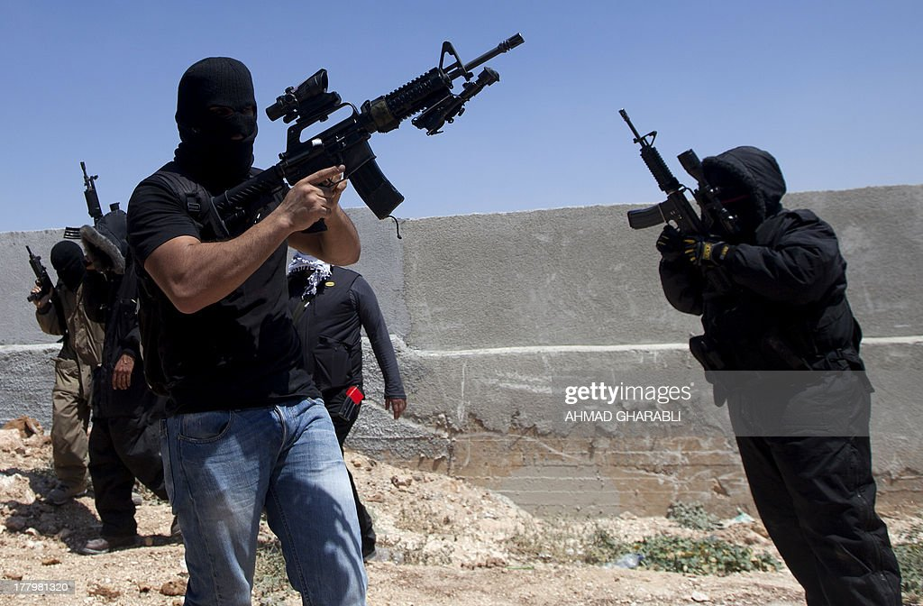 Palestinian militants hold up their automatic machine guns as they fire into the air in the city of Ramallah during the funeral procession of three Palestinian youths who were killed during clashes with Israeli security forces in the West Bank's Qalandia refugee camp on August 26, 2013. Expected peace talks between Israeli and Palestinian negotiators were cancelled after Israeli security forces shot dead three Palestinians during clashes in the West Bank, a Palestinian official said.