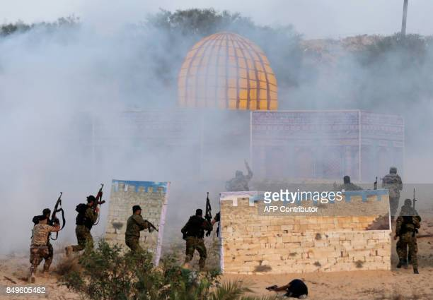 Palestinian militants of alNasser Salah alDeen Brigades the military wing of the Popular Resistance Committees surround a model of the Dome of the...