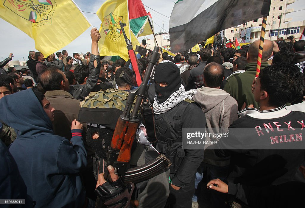 Palestinian militants of the Al-Aqsa Martyrs Brigades stand guard during the funeral of Arafat Jaradat, an inmate who died in an Israeli prison, in the West Bank village of Saair on February 25, 2013. Militants of the Al-Aqsa Martyrs Brigades, the armed wing of Palestinian president Mahmud Abbas' Fatah movement, vowed to avenge the death of Jaradat, a prisoner they say was tortured in an Israeli jail. AFP PHOTO/HAZEM BADER