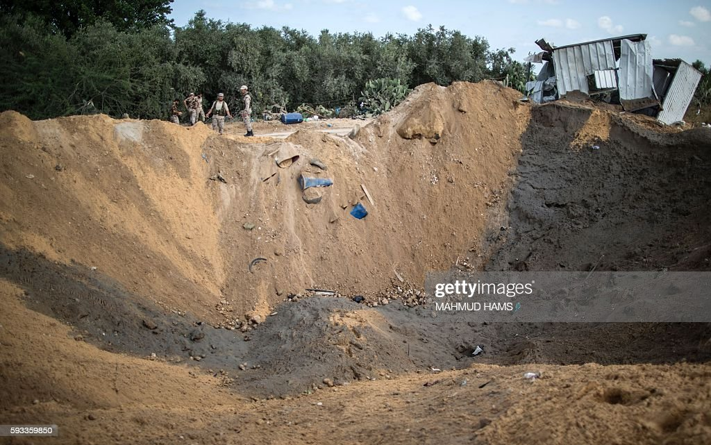 Palestinian militants of the Islamic Jihad movement arrive to inspect a crater on August 22 2016 in Beit Lahia in the northern Gaza Strip following...