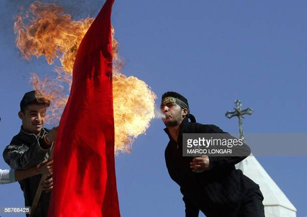 Palestinian militants of the Islamic Jihad movement spews out benzine to set on fire a Danish flag during a demonstrations against the publication in...