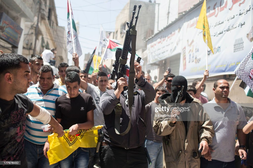 Palestinian militants seen walking and shooting in the air during the funeral procession during the funeral held for three Palestinians killed during IDF operation at Kalandia refugee camp on August 26, 2013 in Ramallah, West Bank. At least 15 people were injured as Palestinians clash with undercover Israeli troops.At least 15 people were injured as Palestinians clash with undercover Israeli troops.