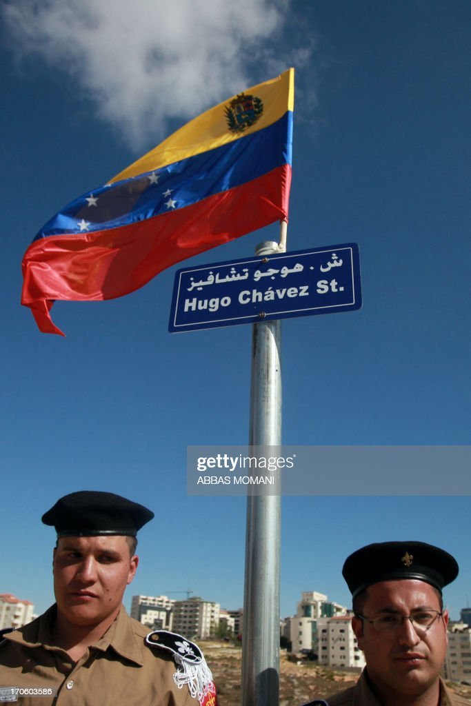 Palestinian military officials stand under a sign flying the Venezuelan flag following the opening of a new street in the name of the late Venezuelan president Hugo Chavez on June 15, 2013, in the West Bank city of Ramallah.