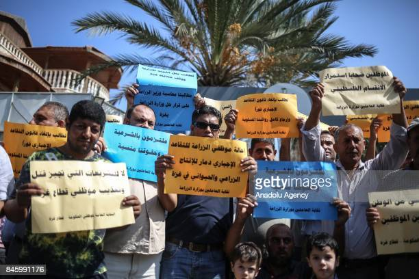 Palestinian Ministry of Agriculture employees hold banners during a demonstration against Palestinian Government's 'obligatory and early retirement...