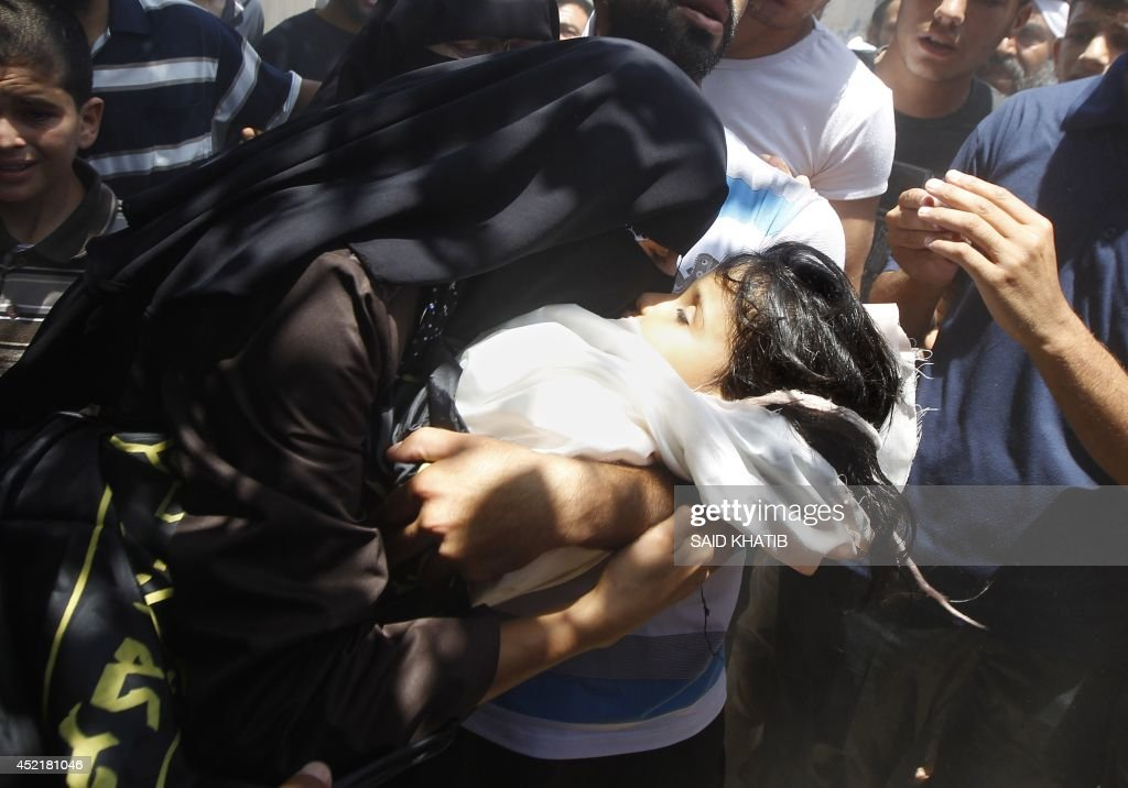 A Palestinian mother kisses the body of four-year-old girl Sarah Sheik al-Eid after she was killed along with her father and uncle in a Israeli military strike the previous day, during their funeral in Rafah in the southern Gaza Strip on July 15, 2014 . Israel carried out at least four air strikes against Gaza on Tuesday afternoon, resuming raids after a truce that failed to get off the ground, AFP correspondents and eyewitnesses said.