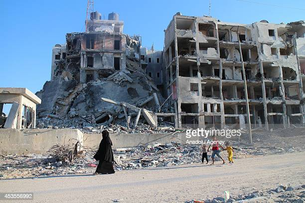 Palestinian mother with her children walk around the ruins of their buildings during a 72hour humanitarian ceasefire in Gaza on August 12 2014
