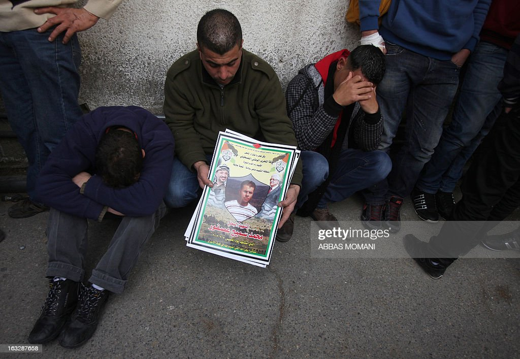 Palestinian mourn outside the hospital where the body of Mohammed Asfour is being held in Ramallah on March 7, 2013 after he succumbed to his injuries from clashes with Israeli troops during a protest in February which erupted following the death of a prisoner in Israeli custody. Asfour, a 22-year-old student studying sports, was seriously wounded by a rubber-coated steel bullet to the head fired by Israeli troops during a demonstration in the West Bank village of Abud on February 23, activists said. AFP PHOTO/ABBAS MOMANI