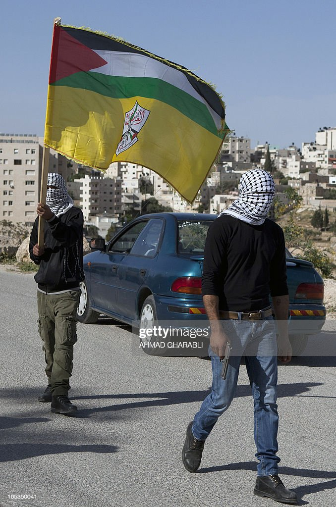 A Palestinian mourner, waving his national flag (top) and the Fatah movement flag (bottom) walks alongside a fellow mourner holding a gun as they escort the body of Palestinian prisoner Maisara Abu Hamdiyeh to the Abu Dis University, on the outskirts of Jerusalem, for a Palestinian autopsy on April 3, 2013. Hamdiyeh, who had served 10 years of a life sentence for attempted murder, died in an Israeli hospital the previous morning two months after being diagnosed with throat cancer.