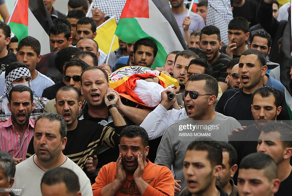 Palestinian mourners attend the funeral of Muayyad Ghazawneh who died following a three week coma after he inhaled tear gas smoke fired by Israeli forces during a weekly demonstration against Israeli occupation of Palestinian land, on March 15, 2013 in al-Ram near Ramallah.