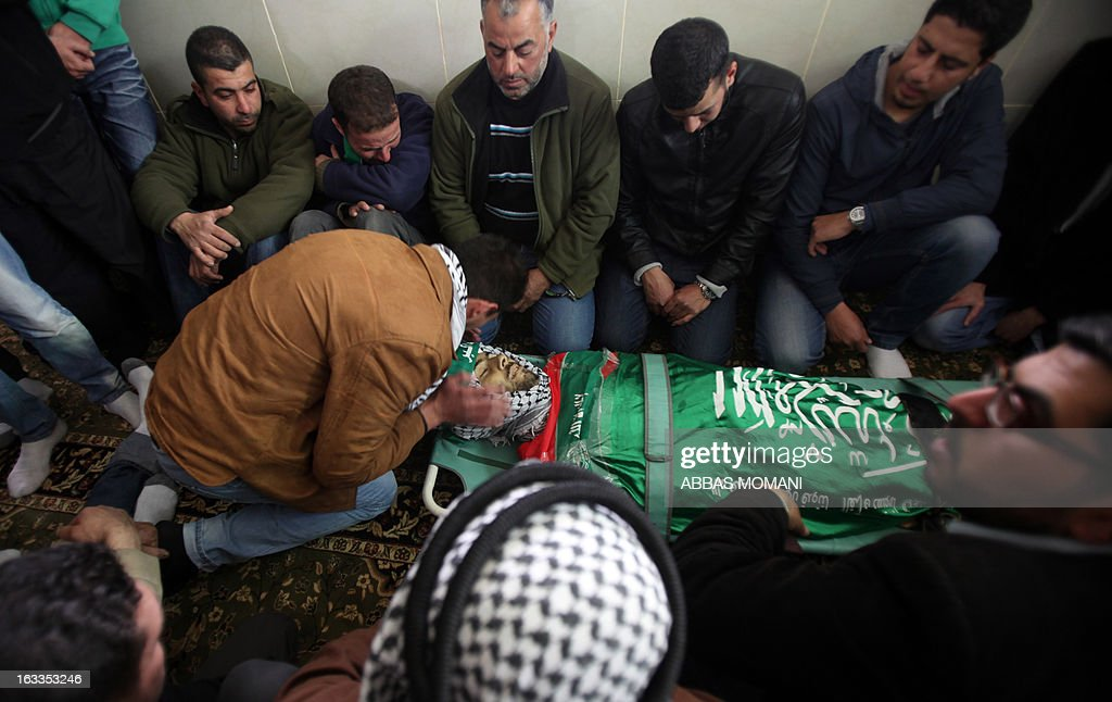 Palestinian mourners bid farewell to Mohammad Asfour, a 22-year-old protester who died of wounds sustained the previous day, during his funeral in the West Bank village of Abud on March 8, 2013. Asfour was wounded in the head by a rubber-coated steel bullet fired by Israeli troops during a protest which erupted after a prisoner died in Israeli custody. AFP PHOTO/ABBAS MOMANI