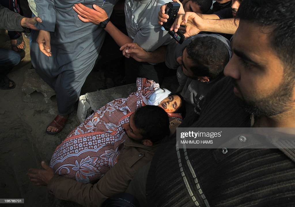 Palestinian mourners bury the body of 10-year-old Palestinian Mohammed Ashour, killed the previous day in an Israeli air strike on Gaza City's Zeitun neighbourhood according to the Hamas ambulance service, during his funeral in the war-battered city on November 21, 2012. Fighting raged on both sides of Gaza's borders despite intensified efforts across the region to thrash out a truce to end a week of violence that has so far cost 136 Palestinian and five Israeli lives. AFP PHOTO/MAHMUD HAMS
