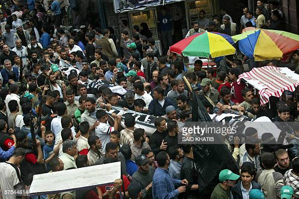 Palestinian mourners carry the bodies of five militants killed yesterday during their funeral in Gaza City 06 May 2006 Five Palestinians were killed...