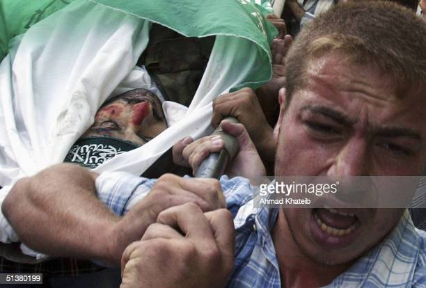 Palestinian mourners carry the body of a family member killed in violent clashes during the Israeli military incursion October 1 2004 in Jabaliya...