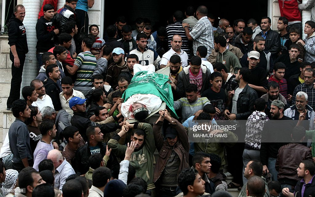 Palestinian mourners carry the body of a man during the funeral of people killed in Israeli air strikes in Maghazi refugee camp in central Gaza Strip on November 17, 2012. Israeli strikes on Gaza killed at least eight Palestinians and destroyed the Hamas government headquarters as Israel called up thousands more reservists for a possible ground war.