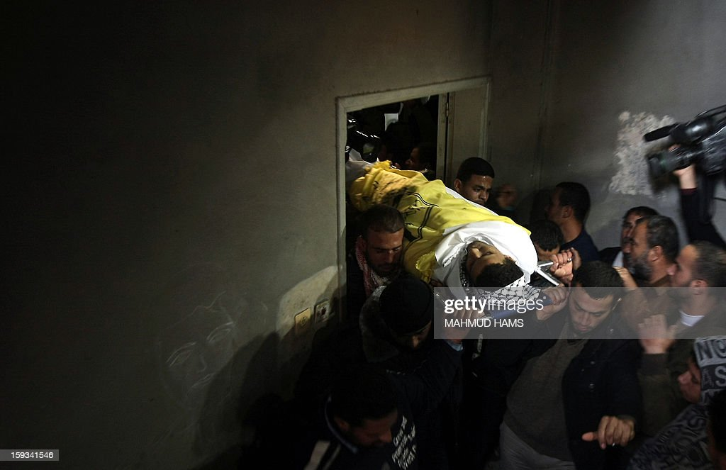 Palestinian mourners carry the body of Anwar Mohammed al-Mamluk during his funeral in Gaza City on January 12, 2013. Israeli soldiers shot dead Mamluk and wounded another in the northern Gaza Strip, a spokesman for the territory's emergency services said. AFP PHOTO/MAHMUD HAMS