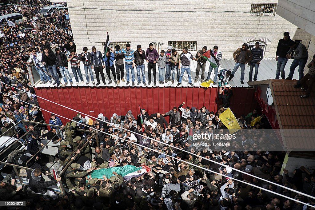 Palestinian mourners carry the body of Arafat Jaradat, an inmate who died in an Israeli prison, during his funeral in the West Bank village of Saair on February 25, 2013. Militants of the Al-Aqsa Martyrs Brigades, the armed wing of Palestinian president Mahmud Abbas' Fatah movement, vowed to avenge the death of Jaradat, a prisoner they say was tortured in an Israeli jail. AFP PHOTO/MARCO LONGARI