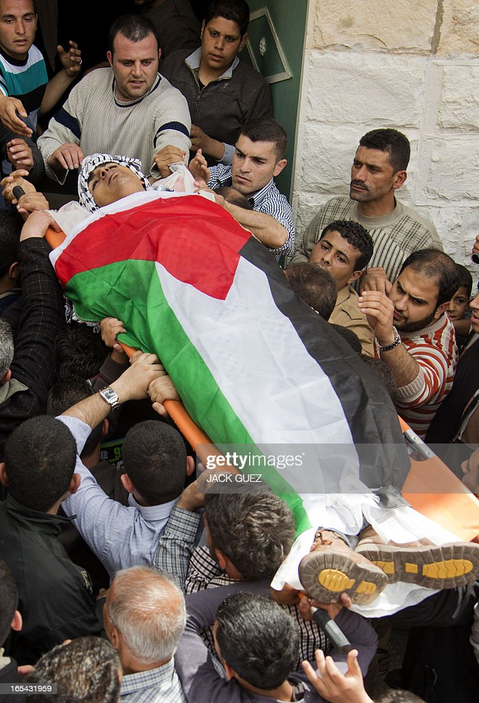 Palestinian mourners carry the body of Naji Balbisi, a 19-year-old shot by Israeli troops, during his funeral in the West Bank town of Anabta near Tulkarem on April 4, 2013. The West Bank simmered with anger as thousands joined the funeral of prisoner Maisara Abu Hamdiyeh who died in an Israeli jail and similar numbers gathered to bury two teens shot dead overnight during clashes over the death of the prisoner, Israeli and Palestinian sources said. AFP PHOTO / JACK GUEZ