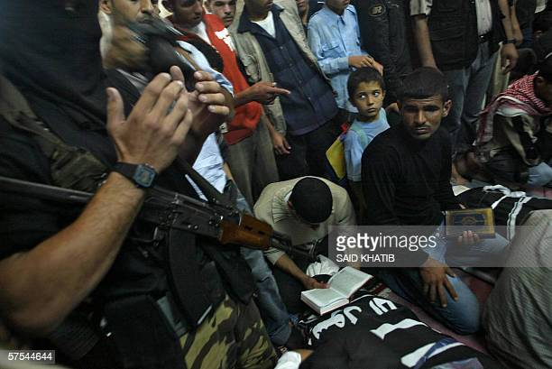 Palestinian mourners pray next to the bodies of five militants killed yesterday during their funeral in Gaza City 06 May 2006 Five Palestinians were...
