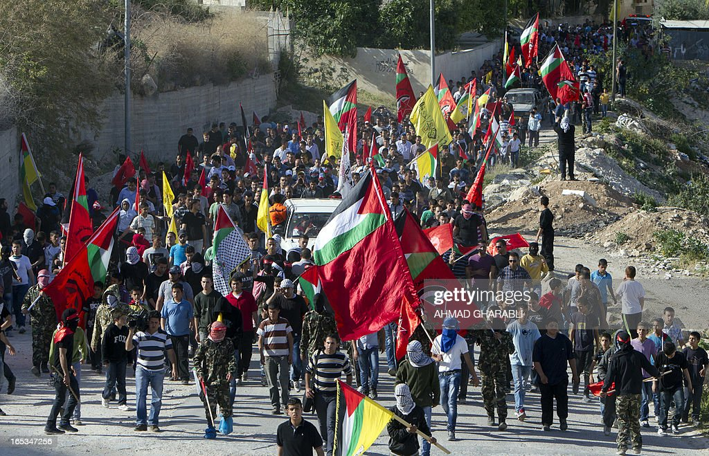 Palestinian mourners, waving their national flag, escort the body of Palestinian prisoner Maisara Abu Hamdiyeh to the Abu Dis university, on the outskirts of Jerusalem, on April 3, 2013. Hamdiyeh, who had served 10 years of a life sentence for attempted murder, died in an Israeli hospital the previous morning two months after being diagnosed with throat cancer.