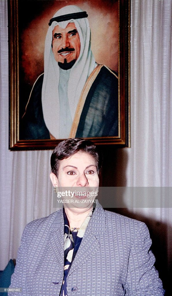 Palestinian MP Hanan Ashrawi stands under a portrait of the emir of Kuwait Sheikh Jaber alAhmad alSabah upon her arrival in Kuwait City 03 May 2002...