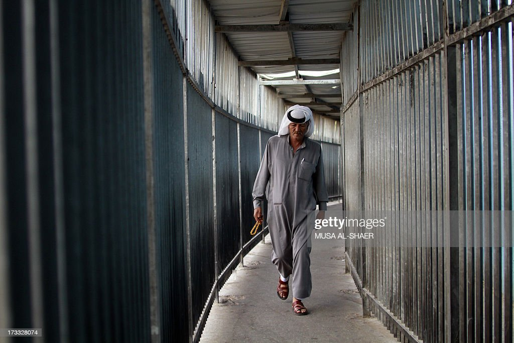 A Palestinian Muslim crosses a checkpoint along Israel's controversial separation barrier on the outskirts of the West Bank town of Bethlehem on July 12, 2013 on his way to Jerusalem to attend the Friday prayers at the Al-Aqsa mosque during the Muslim fasting month of Ramadan.