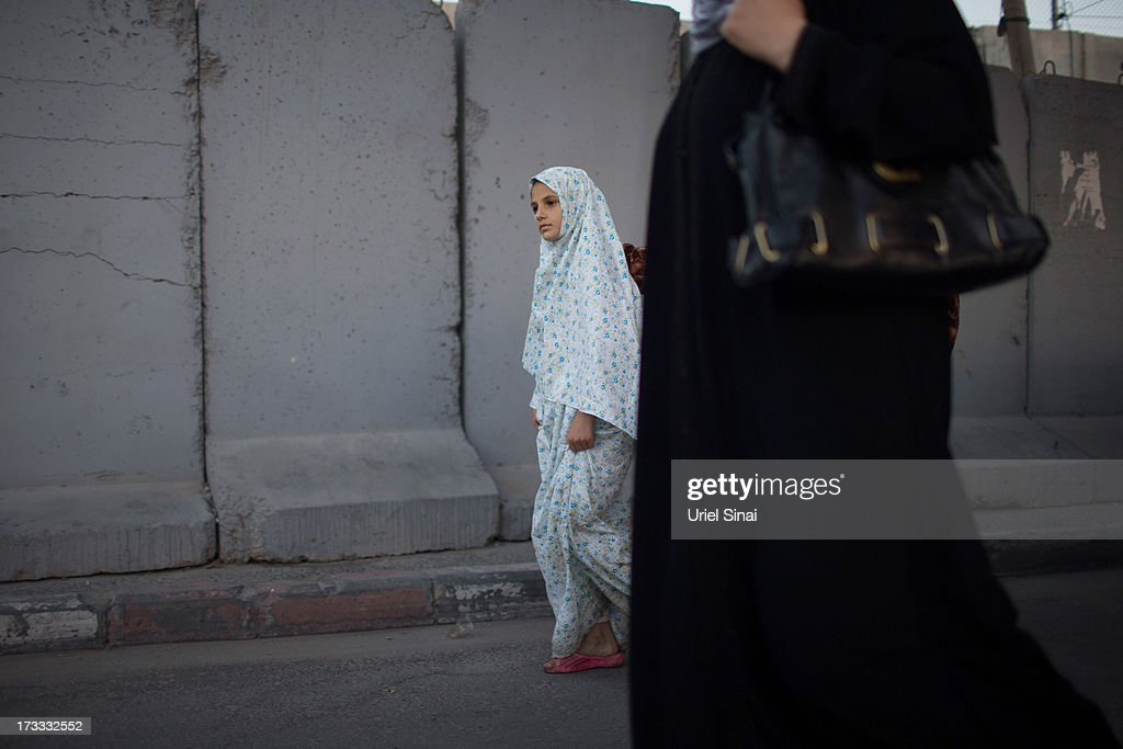 A Palestinian Muslim girl walks past Israel's separation barrier as worshippers cross the Qalandia checkpoint on their way to Jerusalem on July 12, 2013 near Ramallah, West Bank. Thousands of Palestinian worshippers crossed from the West Bank into Israel to attend the first Friday prayers of Ramadan at the the Al-Aqsa mosque compound in Jerusalem. Ê