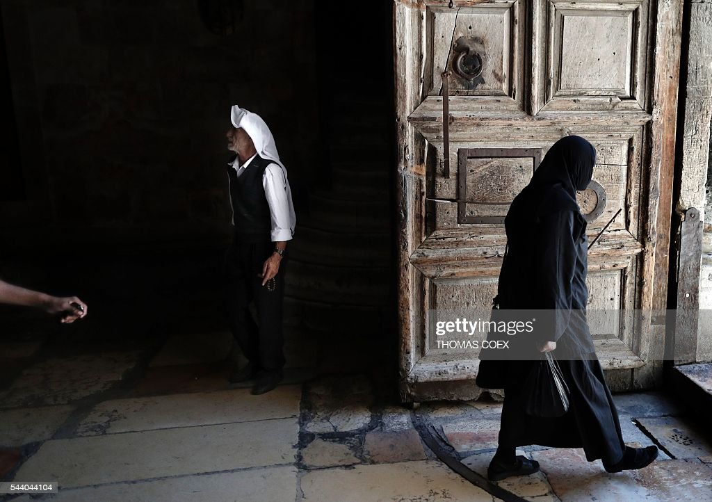 A Palestinian Muslim man (C) visits the Church of the Holy Sepulchre in Jerusalem's Old City on July 1, 2016. / AFP / THOMAS