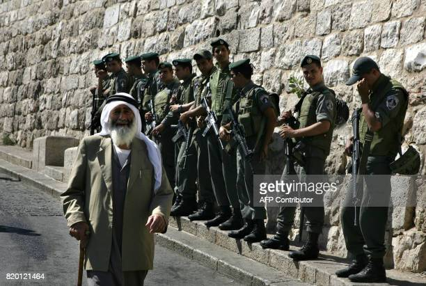 A Palestinian Muslim man walks past Israeli border guards standing close to Lion's Gate which leads to the the alAqsa mosque compound in Jerusalem's...