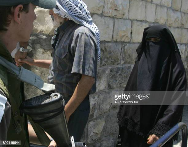 A Palestinian Muslim orthodox woman walks past an Israeli border police officers as she enters the old city of annexed east Jerusalem 14 July 2006...