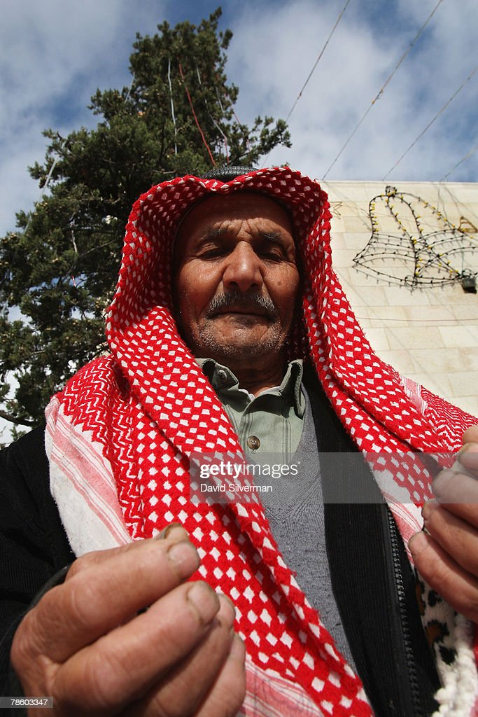 A Palestinian Muslim performs his midday Friday prayers in front of Christmas decorations in Manger Square on December 21, 2007 in Bethlehem in the West Bank. The biblical town is celebrating both Christmas and the Muslim Eid al-Adha over the next few days.