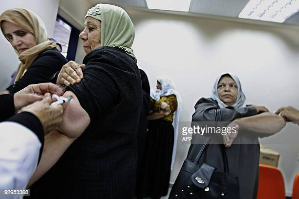 Palestinian Muslim pilgrims receive H1N1flu vaccination at the Rafah border crossing with Egypt as worshippers head to the annual pilgrimage to the...
