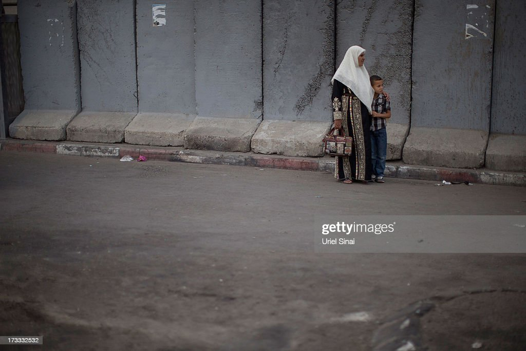 A Palestinian Muslim woman and her son stand in front of Israel's separation barrier as worshipers cross the Qalandia checkpoint on their way to Jerusalem on July 12, 2013 near Ramallah, West Bank. Thousands of Palestinian worshipers crossed from the West Bank into Israel to attend the first Friday prayers of Ramadan at the the Al-Aqsa mosque compound in Jerusalem.