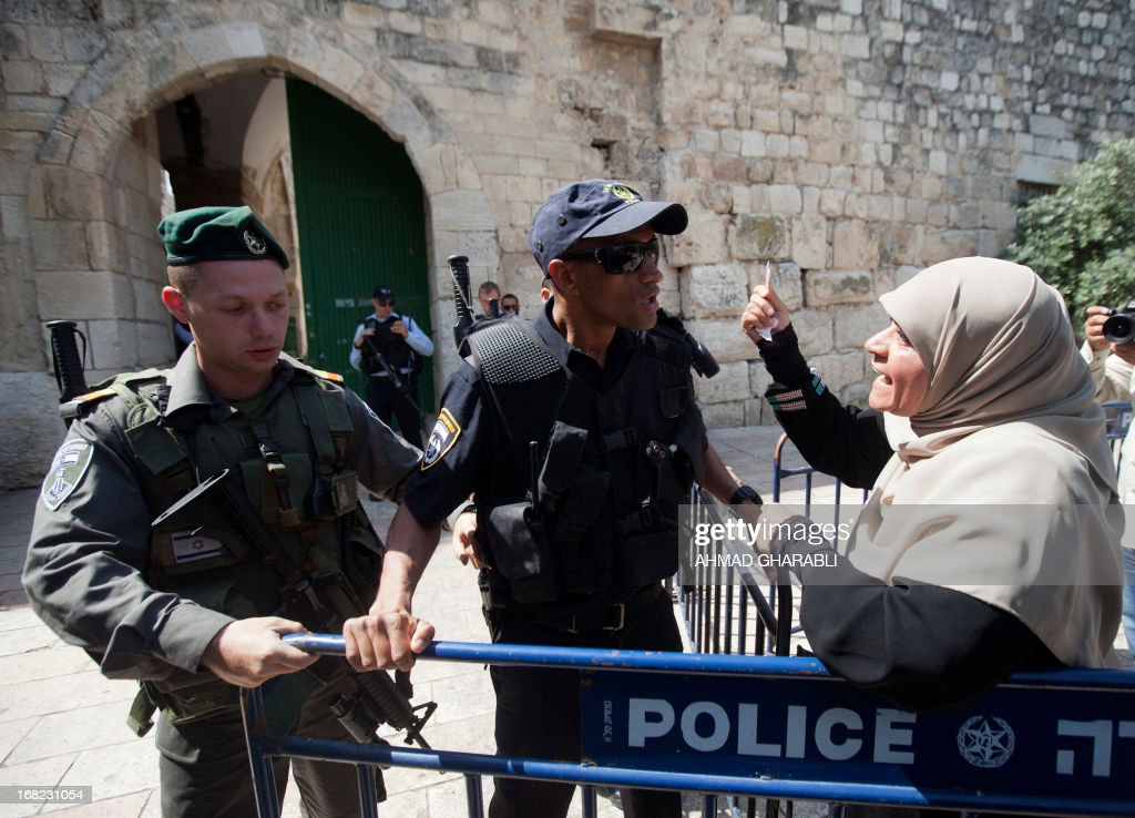 A Palestinian Muslim woman argues with an Israeli policeman as security forces stand guard outside the al-Aqsa mosque compound at Lion's Gate in Jerusalem's Old City on May 7, 2013 restricting the number of Muslim worshipers entering the holy site.